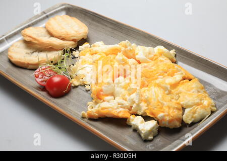 Scrambled eggs wioth some bread and cherry tomatoes - Stock Image