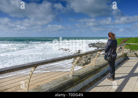 A woman standing alone on a windy day on a balcony overlooking Fistral Beach in Newquay in Cornwall. - Stock Image
