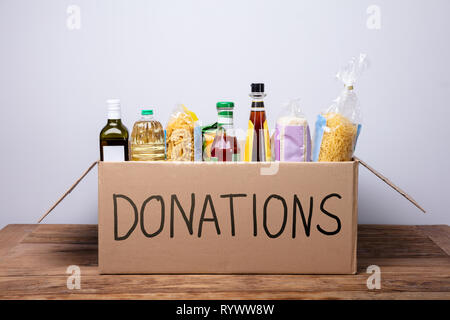 Close-up Of A Donation Box With Various Food Items On Wooden Desk - Stock Image