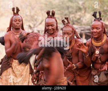 Africa, Namibia, Opuwo. Himba women watch dancer. Credit as: Wendy Kaveney / Jaynes Gallery / DanitaDelimont.com - Stock Image