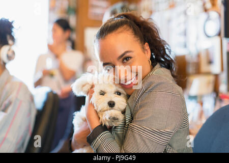 Portrait happy businesswoman with cute dog in office - Stock Image