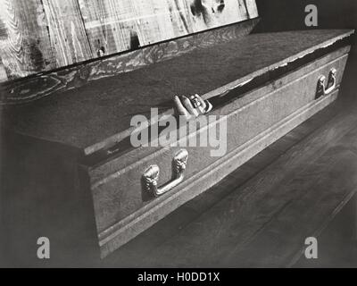 Hand reaching out of coffin - Stock Image