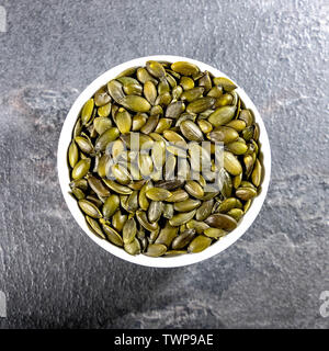 Looking Down on a Bowl of Healthy Dried Pumpkin Seeds With No People - Stock Image
