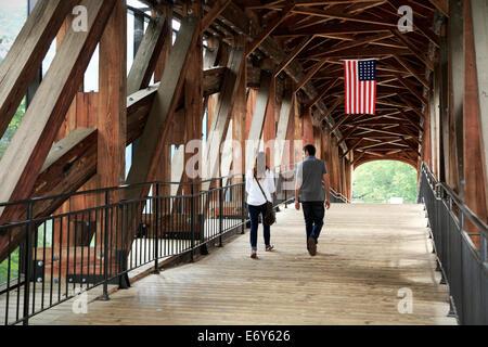 Old Salem, North Carolina. Young couple walks on covered bridge. - Stock Image