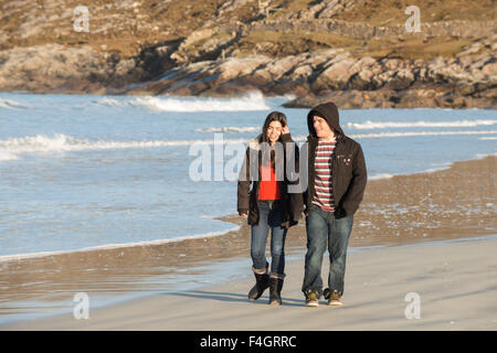 Young couple walking on a beach - Stock Image