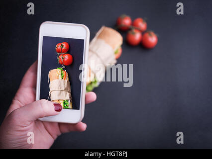 Human hand using smart phones to take photos of sandwich on black background. Mobile phone food photography - Stock Image