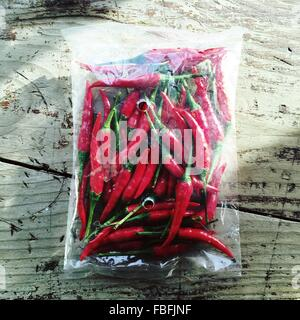 High Angle View Of Red Chili Peppers In Bag On Table - Stock Image