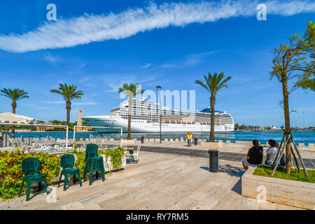 Tourists watch as a massive cruise ship pulls into the narrow port on the Adriatic Sea in the mediterranean city of Brindisi, Italy, in Puglia region - Stock Image