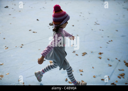 Girl aged four with knitted woollen bobble hat running through empty blue paddling pool filled with autumnal leaves - Stock Image