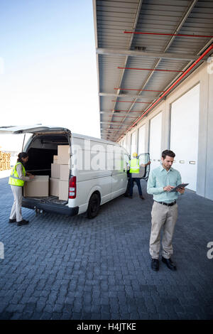 Manager working on tablet and warehouse workers loading the cardboard boxes - Stock Image