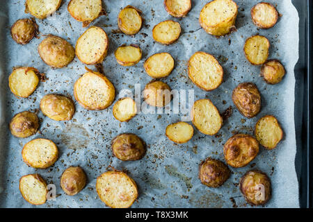 Baked Potato Slices in Oven Tray with Salt and Pepper. Organic Food. - Stock Image