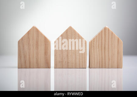 Close-up Of Wooden Houses Arranged In Row On White Desk - Stock Image