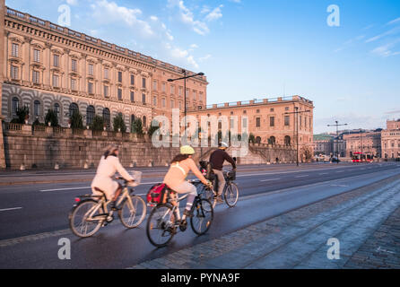 Three cyclists on a cycle lane on Skeppsbron road passing the Royal Palace, Gamla Stan, Stockholm, Sweden - Stock Image