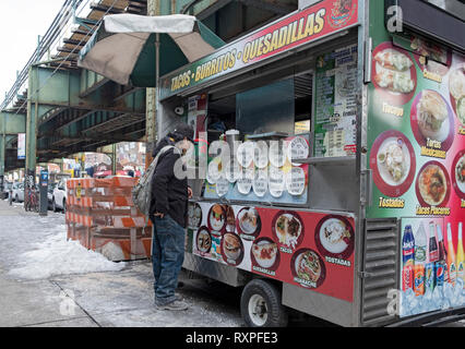 A Latin American worker stops to buy food from a Mexican food cart parked on Roosevelt Ave. under the elevated subway. In Jackson Heights, Queens, NYC - Stock Image