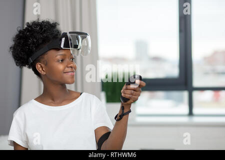 Mixed-race african woman with short curly hair and pleasant smile wears virtual reality goggles, holds remote controllers, standing at home - Stock Image