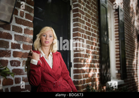 A young woman stands at the front door of her home, Charleston, South Carolina, USA - Stock Image