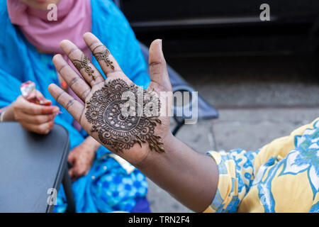 A woman from the Islamic Republic of Mauritania gets her right hand decorated with henna to celebrate the end of Eid. In Jackson Heights, Queens, NYC - Stock Image