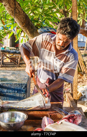 Galle, Sri Lanka - March 14th 2011:  Man cutting fish slices on the market on the beach. Fishermen sell their own catch here. - Stock Image
