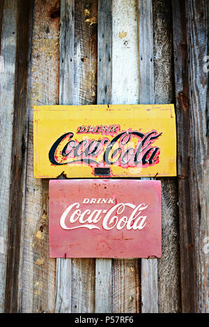 Old antique or vintage Coca-Cola advertising signs tacked up on the side of an old wooden cabin in rural Alabama. - Stock Image