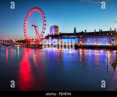 London Eye and County Hall, on the South Bank of the Thames, illuminated at twilight. - Stock Image