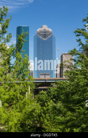 Heritage Plaza Houston skyline through trees on sunny day with blue sky - Stock Image