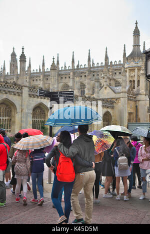 groups of foreign tourists with a tour guide gather outside Kings College in Cambridge with their colourful umbrellas - Stock Image