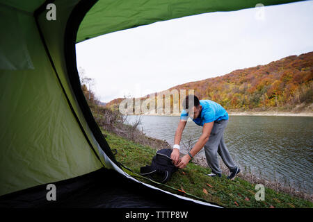 Man opening backpack by river - Stock Image