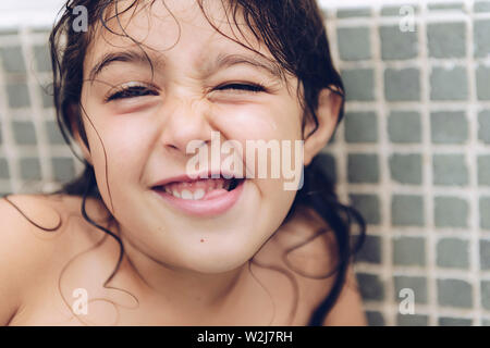portrait of a happy pretty little girl grimacing while taking a bath in the bathtub, kids hygiene concept - Stock Image
