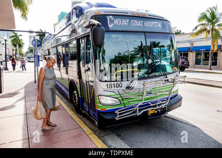 Miami Beach Florida Washington Avenue Miami-Dade Metrobus public transportation stop woman passenger carrying plastic shopping bags waiting to board - Stock Image