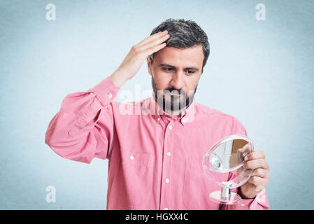 Man worried about gray hair looking in a mirror - Stock Image