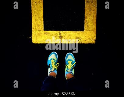 Feet outside yellow square paint - Stock Image