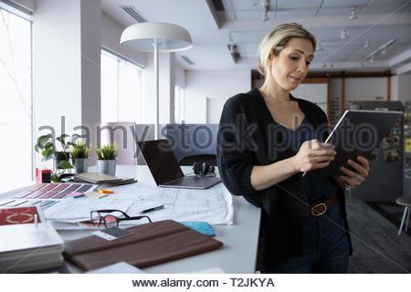 Female interior designer using digital tablet in design studio - Stock Image
