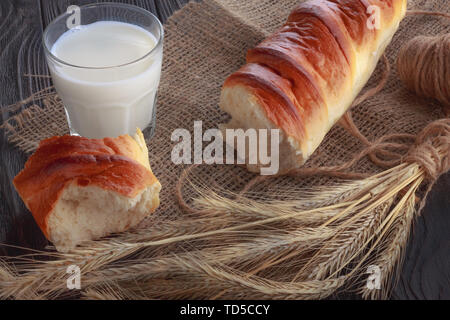Baguette with a piece broken off next to a glass of fresh milk on the table. Breakfast - Stock Image