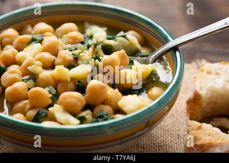 Chickpea soup with spinach and dry salted cod in a rustic bowl. Traditional spanish recipe in the Holy Week. - Stock Image