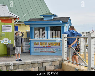 Young male boy taking a picture or a photo of an adult couple or parents at the tourist resort HarborWalk Village and Marina in Destin Florida USA. - Stock Image