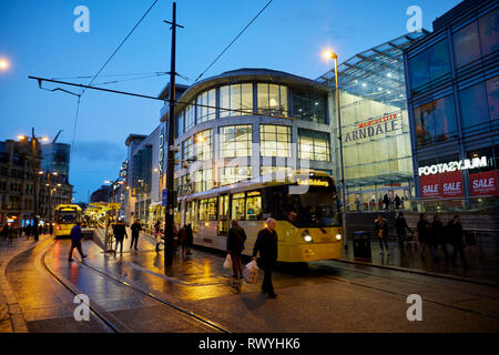 Wet and dark at Exchange Square and Manchester Arndale shopping centre mall entrance as a Metrolink tram departs - Stock Image
