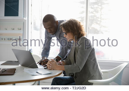 Business people using laptop in conference room meeting - Stock Image