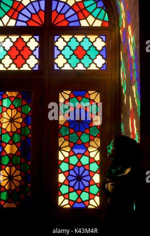 Sunlight illuminates the stained glass of the winter prayer hall of the Nazir ul Mulk Mosque Shiraz Iran. Portrait of Muslim woman - Stock Image