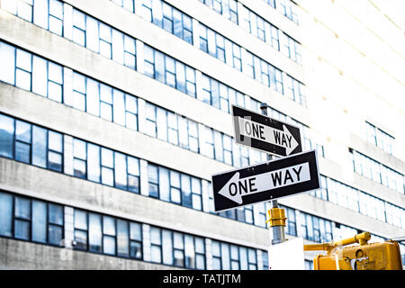 Close-up view of 'one way' road sign with blurred building in the background. Manhattan, New York City, United States of America. - Stock Image