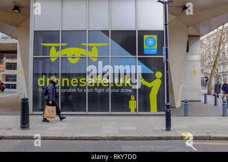London, UK. 23 Feb, 2019. A woman walks past a sign warning drone operators about the law, painted outside the offices of the  Civil Aviation Authorit - Stock Image