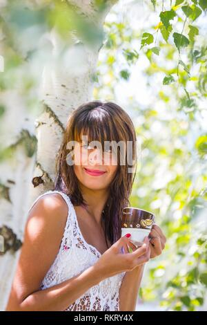 Attractive teenager girl is drinking coffee in nature smiling looking away aside - Stock Image