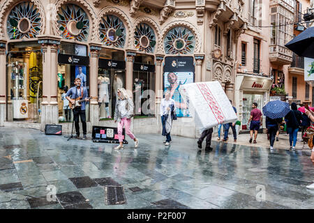Street scene with the street artist and the matrass in front of a modernist building next to Plaza Cort in the old town of Palma - Stock Image