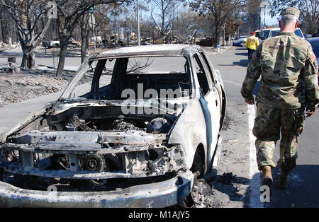 A Cal Guard soldiers walks by the charred remains of a car in Santa Rosa, California, Oct. 14, 2017 (Army National - Stock Image