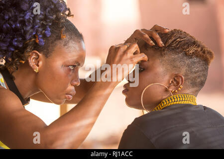 Yako, Burkina Faso; Working on eyelashes at a beauty salon. - Stock Image