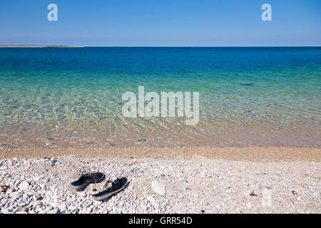 Pair of sandals on a pebble stone beach - Stock Image