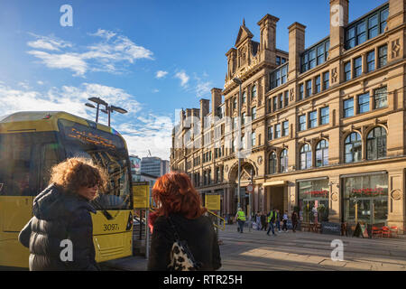 2 September 2018: Manchester, UK - Exchange Square, with Corn Exchange building, Metrolink tram, two young women with backlit hair, and flare. - Stock Image