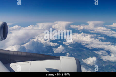 View out of an airplane over a row of anvil-shaped cumulonimbus clouds. - Stock Image