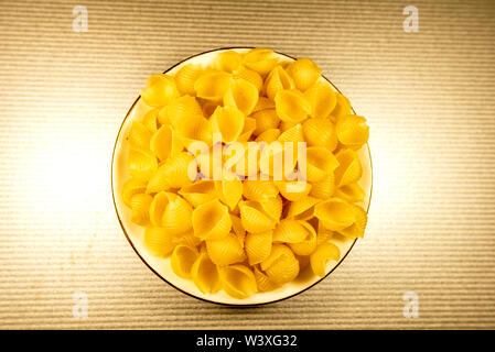 CONCHIGLIONI Italian dry raw pasta Top view. Selective focus with copy space for text. - Stock Image