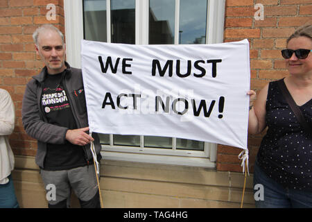 Activists from the Climate Change group Extinction Rebellion hold a banner saying ÒWe Must Act NowÓ during a demo outside Derby City Council house on 22/05/2019 - Stock Image