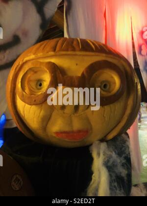Intricate carved pumpkin of a woman's face with glasses and lipstick - Stock Image